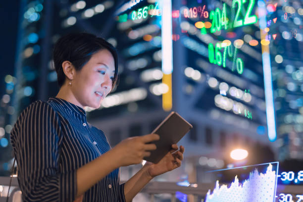 Asian businesswomen checking stock market data on tablet before Hong Kong financial display board stock photo