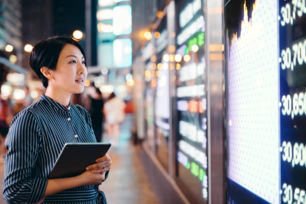 le imprenditrici asiatiche controllano i dati del mercato azionario su tablet prima della scheda di visualizzazione finanziaria di hong kong - mercato luogo per il commercio foto e immagini stock