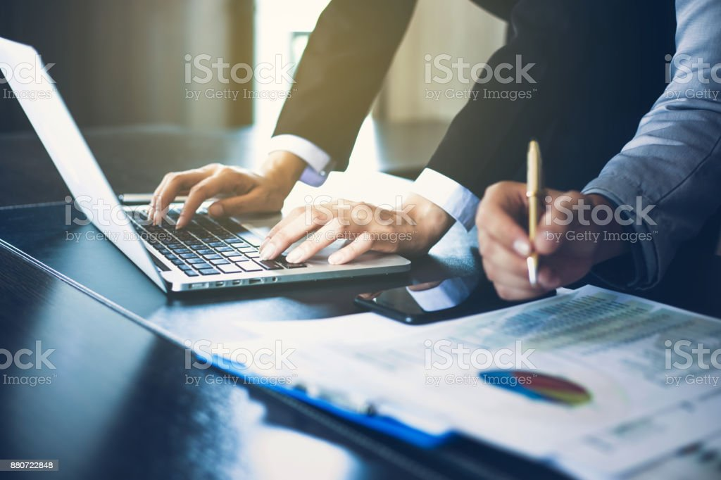 Asian businesswomen holding a pen and analysis documents on office table with laptop computer and graph financial diagram working in the background stock photo