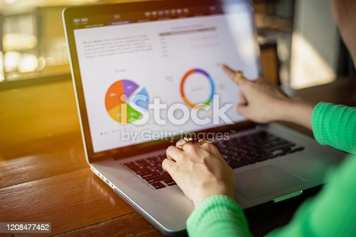 Asian businesswomen using notebook for analysis documents and graph financial diagram working