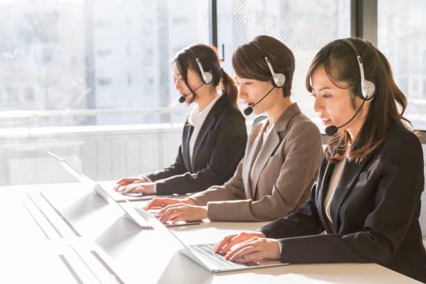 オフィスで働くアジアのビジネスウーマン - コールセンター ストックフォトと画像