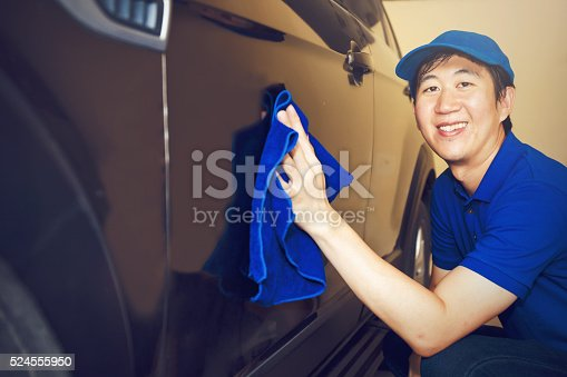 istock Asian Car Cleaner in blue uniform, washing car with smile 524555950