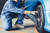 istock Asian car mechanic technician holding clipboard and checking to maintenance vehicle by customer claim order in auto repair shop garage. Wheel tire repair service. People occupation and business job 1222187950