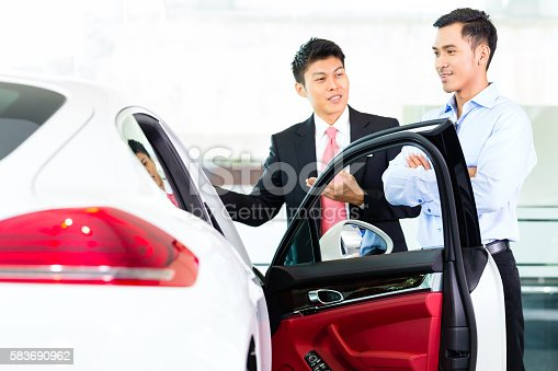 istock Asian Car Salesman selling auto to customer 583690962