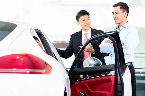istock Asian Car Salesman selling auto to customer 583690962
