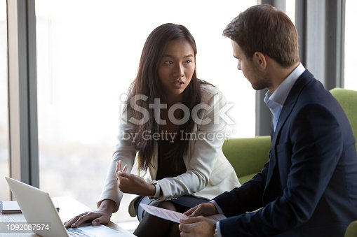Serious asian businesswoman and caucasian businessman in formal suit sitting together on couch using computer talking discussing solving business issues having problem searching looking for solution