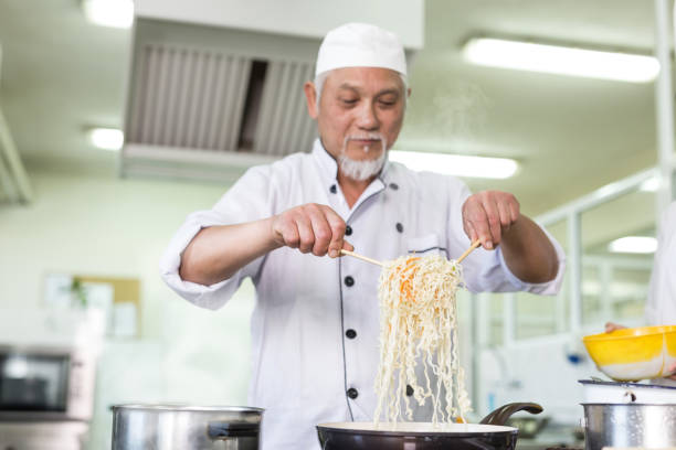Asian chef preparing noodles in restaurant stock photo