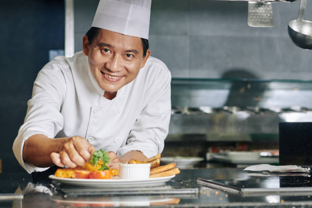 Asian chef with dish at the restaurant stock photo