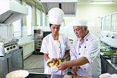 Chef cooking in asian restaurant, with his female assistant.