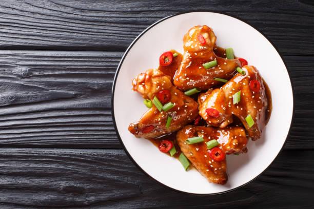 alitas de pollo asiáticas en salsa teriyaki de cerca en un plato. vista superior horizontal - sésamo fotografías e imágenes de stock