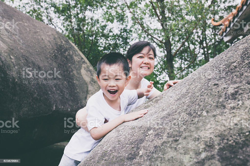 Asian child and mother cheering beside mountain stone stock photo