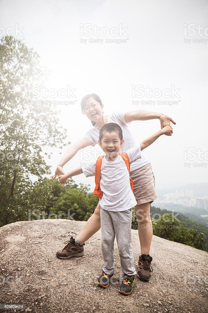 Asian child and mother cheering on mountain peak stock photo