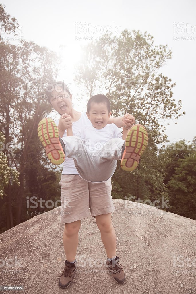 Asian child and mother playing on mountain peak stock photo