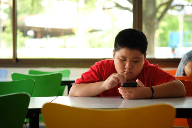 Asian child Boy are addictive playing tablet and mobile phones, Game Addiction stock photo