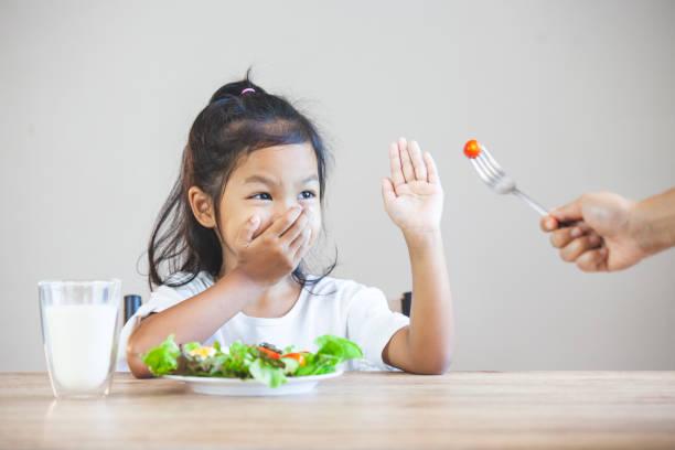Asiatisches Kind mag kein Gemüse essen und sich weigern, gesundes Gemüse zu essen – Foto