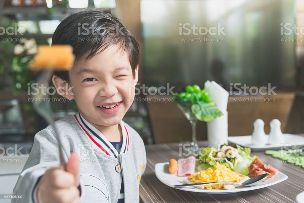 Asian child eating breakfast stock photo