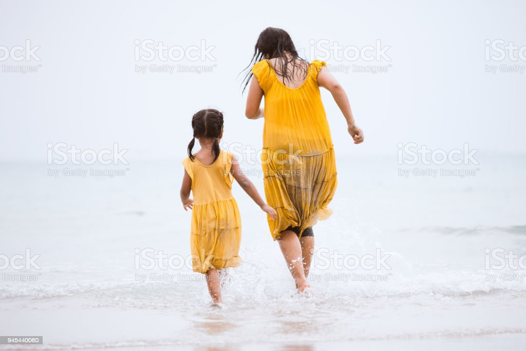 Asian child girl and her mother running and playing together in the sea in summer vacation stock photo