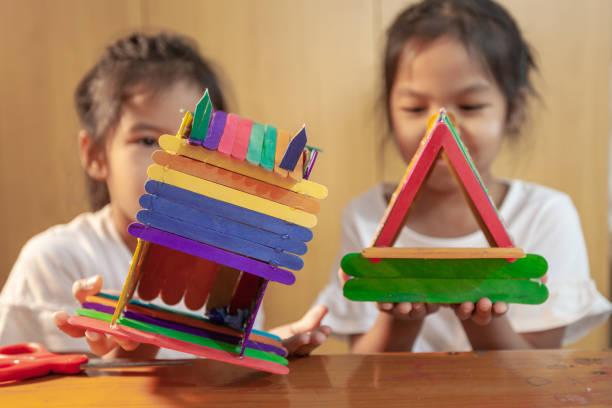 Asiatische Kind Mädchen kleben farbige Eisstöcke von Heißschmelze elektrische Klebepistole. Kinder haben Spaß, Haus auf einem Bastelprojekt zu machen. – Foto