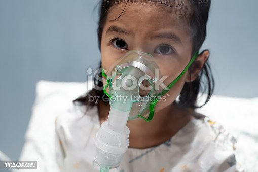 Asian child girl has asthma or pneumonia disease and need nebulization by get inhaler mask on her face