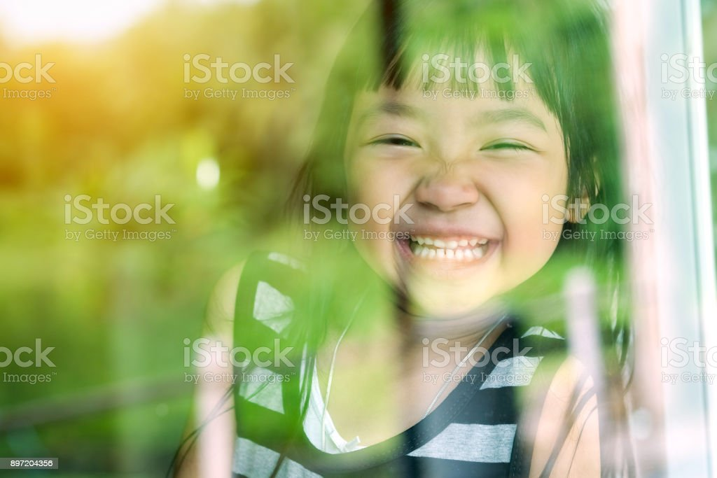 Asian child girl standing on glass mirror reflecting green forest. She was smiling in a good mood. stock photo