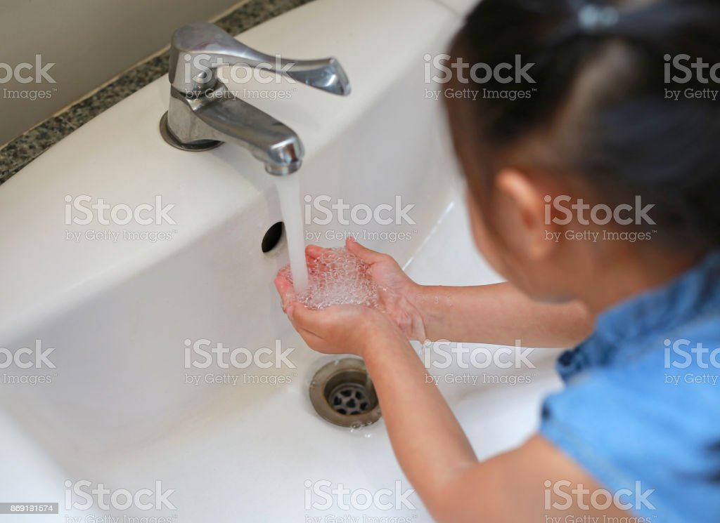Asian Child girl washing Hands in water sinks.