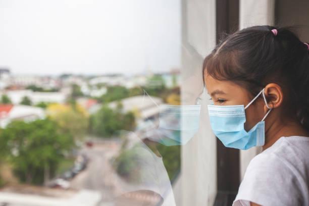 Asiatische Schild Mädchen trägt Schutzmaske blick nach draußen durch das Fenster und bleiben zu Hause Quarantäne von der Coronavirus Covid-19 und Luftverschmutzung pm2.5. – Foto