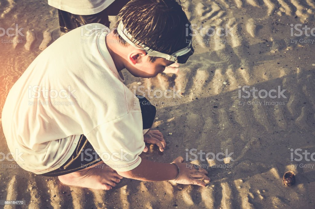 Asian child has fun digging in the sand. Young boy enjoying on beach. royalty-free stock photo
