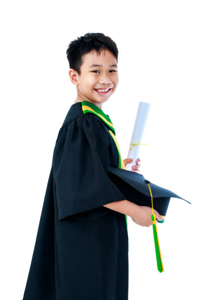 Asian child in graduation gown with diploma certificate and cap smiling happily. stock photo