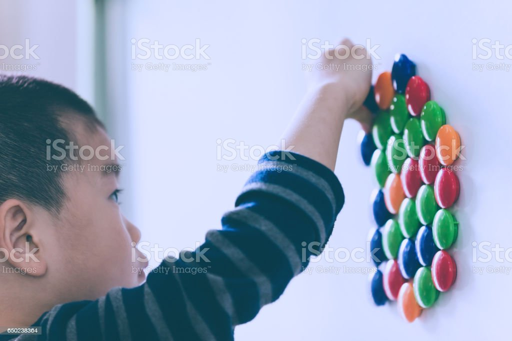 Asian child learning words with magnets stock photo
