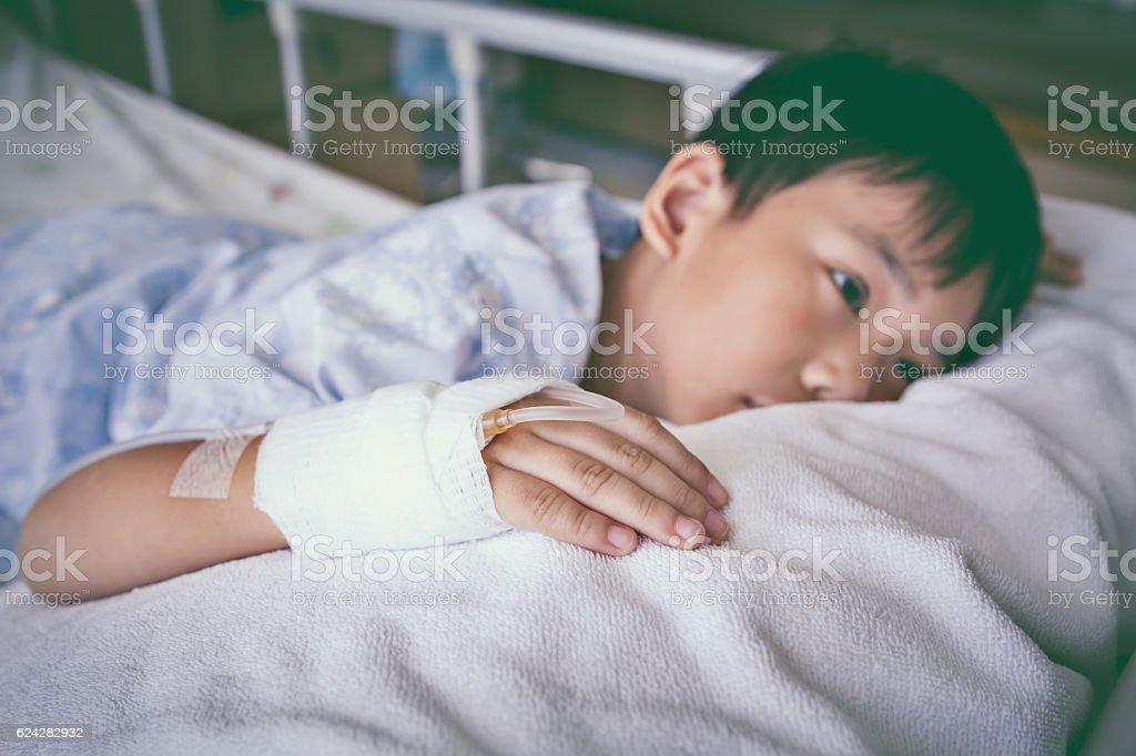 Asian child lying on sickbed, saline intravenous (IV) on hand. stock photo