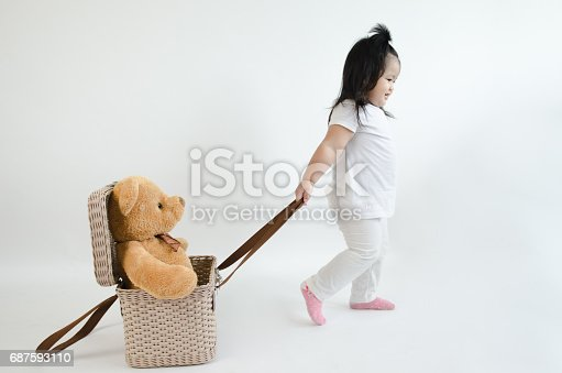 istock Asian child play pull bear doll in the basket 687593110