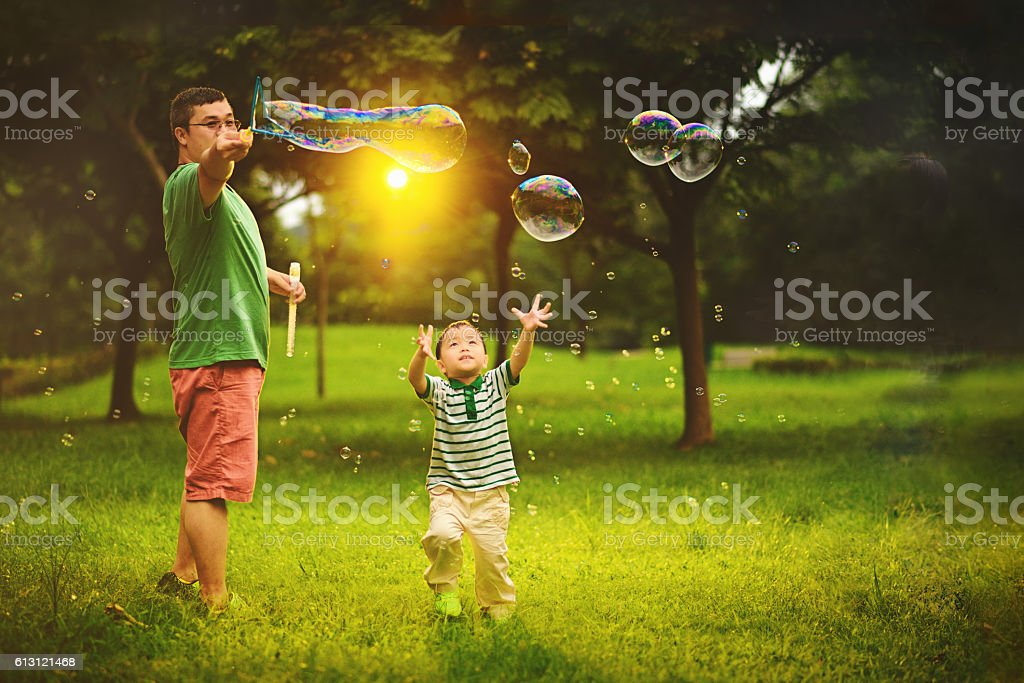 Asian child playing bubble wand with father stock photo