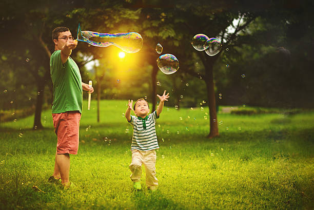 asian child playing bubble wand with father - singapore nature stock photos and pictures