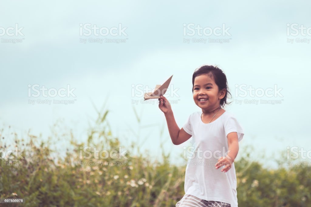 asian child playing toy paper airplane in the meadow stock photo