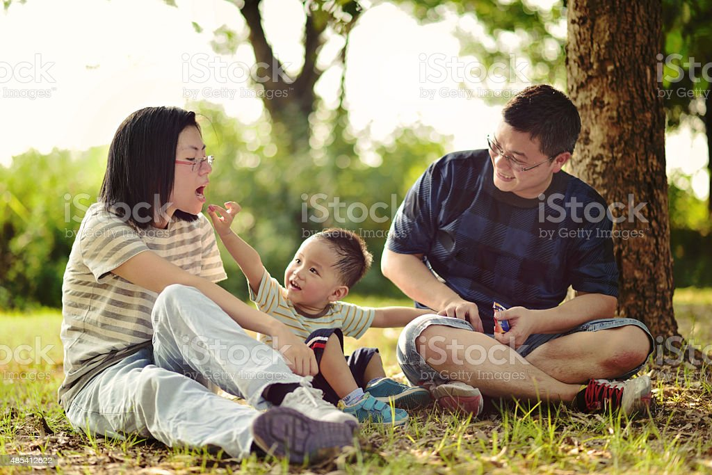 Asian child playing with parents stock photo
