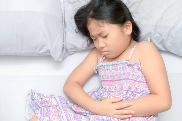 asian child suffering from stomachache stock photo