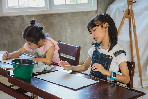Asian children girl drawing with pencils on paper at home or elementary school, Back to school and education concept