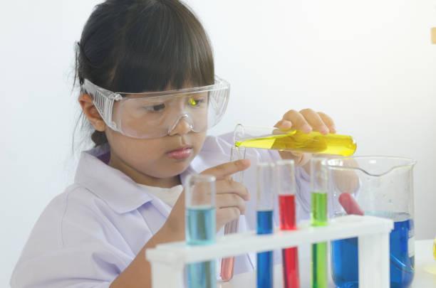 Asian children girl testing chemical in laboratory. stock photo