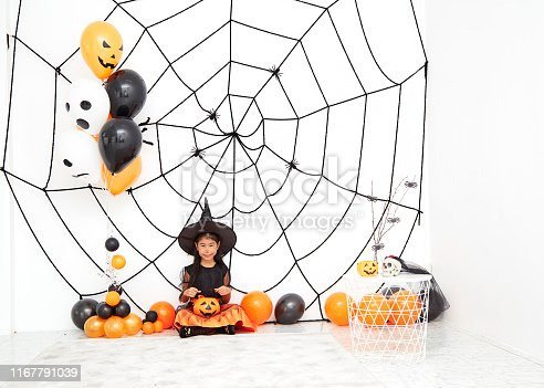 The concept of Halloween, funny face. Funny asian children girl in witch dress costume for Halloween decoration with pumpkins and holiday attributes. Children's party. Cute little witch dressed in hat with a pumpkin.
