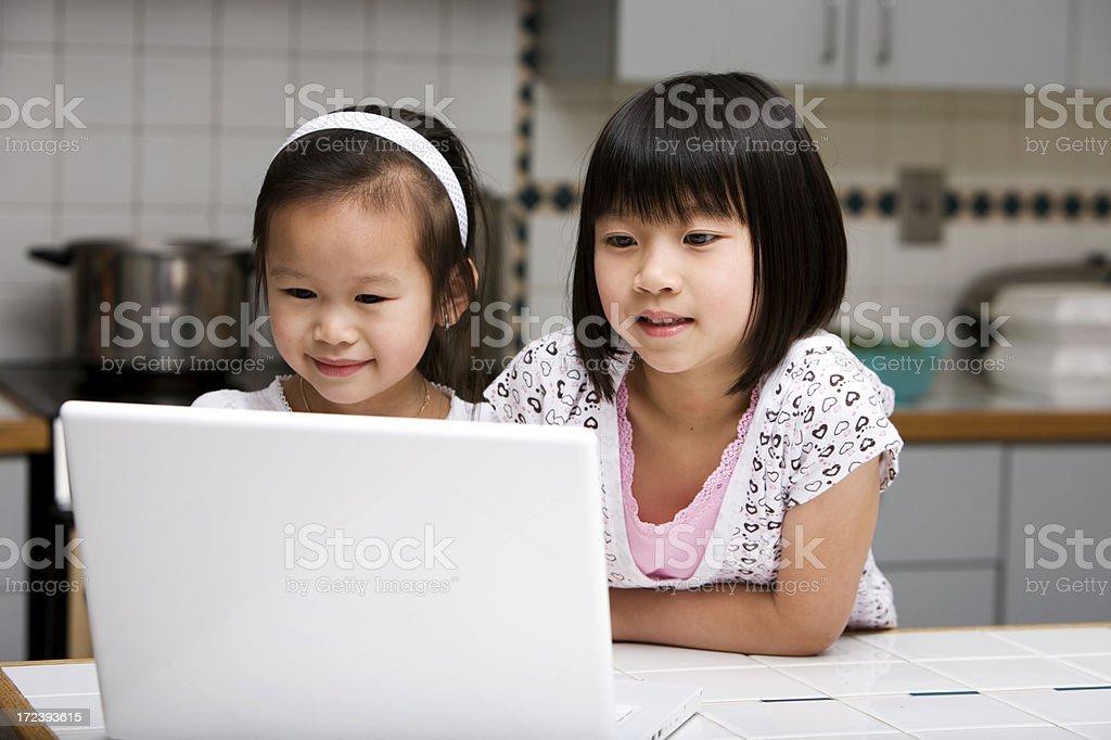 Asian Children Using Laptop at Home in Kitchen, Copy Space royalty-free stock photo