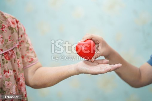 Asian children young kid hold touch and give red heart strong health to old mother lady hands with love, happy, care, encourage and empathy.