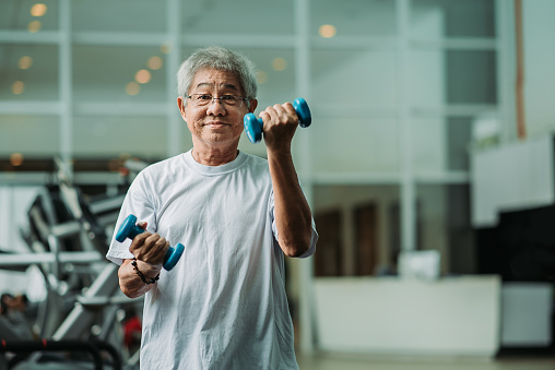 Asian chinese active senior male exercising and workout with dumbbell in gym room during weekend activity
