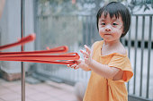 istock asian chinese baby boy holding clothe hanger looking at camera   in front of house during summer weekend 1330375324