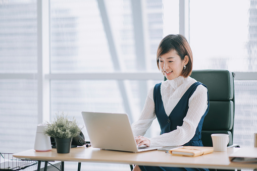 asian chinese beautiful female manager working using her laptop typing in the office