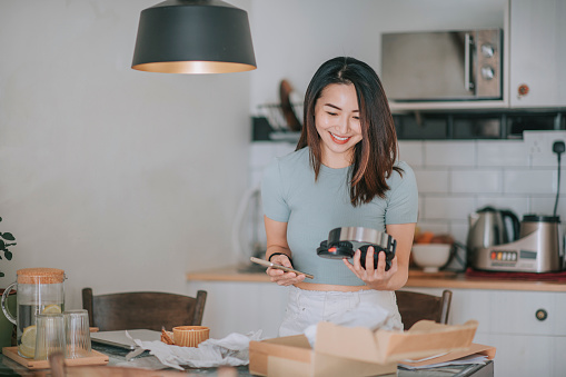 asian chinese beautiful woman receiving unpacking trying on her headphone from online shopping at kitchen