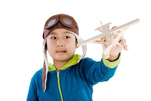asiatische chinesische jungen spielen mit hölzernen flugzeug - zukunftswünsche stock-fotos und bilder