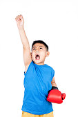 Asian Chinese boy wearing boxing gloves with victory in isolated plain white background.