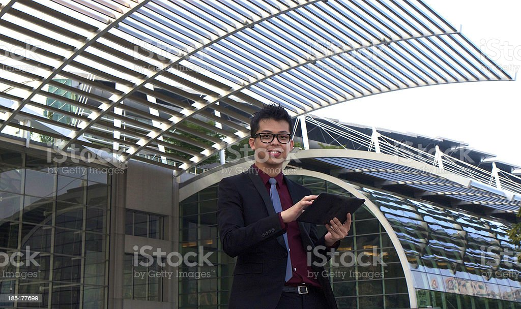Asian Chinese businessman holding a digital tablet royalty-free stock photo