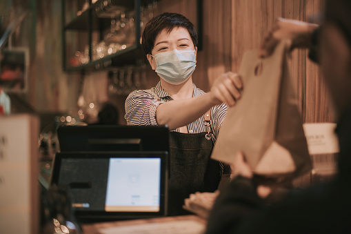 asian chinese cafe owner cashier passing food in recycled paper bag man to delivery person  picking up take away food and putting inside thermo bag at cafe