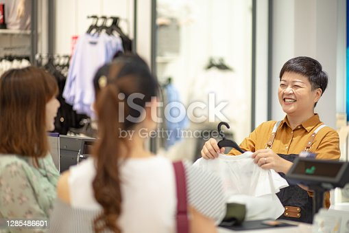 Asian chinese cashier helping customer checkout their selected clothes at counter.